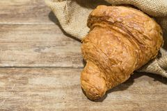 Fresh butter croissant in gunny sack cloth. On wooden table, close up shot Stock Image