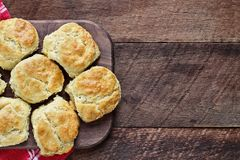 Buttermilk Southern Biscuits on Cutting Board Over Rustic Wood Table. Fresh buttermilk southern biscuits or scones over a rustic wooden table shot from above royalty free stock photo