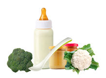 Fresh cabbage, broccoli, baby food, spoon and and milk bottle Stock Photos