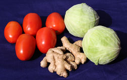 Fresh cabbage, ginger and red  tomatoes. On blue background Stock Photos