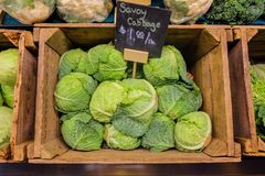 Fresh cabbage vegetable in wooden box stall in greengrocery with price chalkboard label.  Royalty Free Stock Photos