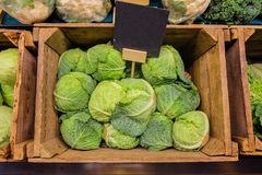 Fresh cabbage vegetable in wooden box stall in greengrocery with price chalkboard label.  Stock Photos