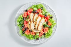 Fresh Caesar salad with chicken, olives and tomatoes stock photo