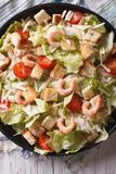Fresh Caesar salad with shrimps closeup vertical top view Stock Images