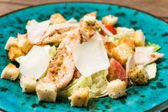 Fresh caesar salad in green plate on wooden table stock photography