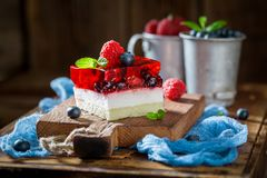 Fresh cake with jelly and berry fruits. On old wooden table Royalty Free Stock Photo