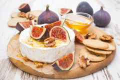 Fresh camembert cheese with honey, figs and crackers Royalty Free Stock Photography