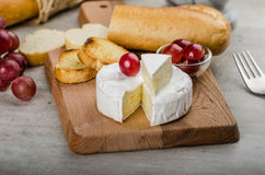 Fresh camembert from organic farms. With red grapes and toasted baguette Royalty Free Stock Photography
