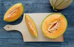 Cantaloupe melons. Fresh cantaloupe cut into pieces on wooden table stock images
