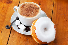 Fresh cappuccino and doughnut with white frosting Stock Images