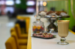 Fresh cappuccino with some sweets. A cup of fresh hot cappuccino with a beautiful topping of beige and brown powder. Fragrant coffee with some sweets on a royalty free stock image