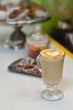 Fresh cappuccino with some sweets. A cup of fresh hot cappuccino with a beautiful topping in the form of a heart. Fragrant coffee on a background of somesweets royalty free stock image