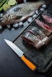 Fresh carp on a dark background with greens and vegetables. Cut into pieces carp on a wooden board stock photo