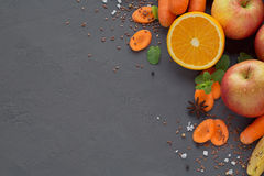 Fresh carrot, apple, pumpkin, orange, grapefruit on dark table. Royalty Free Stock Images