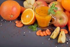 Fresh carrot, apple, pumpkin, orange, grapefruit on dark table. Royalty Free Stock Images