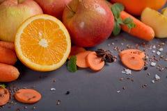 Fresh carrot, apple, pumpkin, orange, grapefruit on dark table. Royalty Free Stock Photo