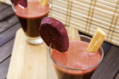 Fresh carrot and beetroot juice in glass decorated with carrot and beetroot slices on wooden tray and bamboo background selective Royalty Free Stock Images