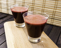 Fresh carrot and beetroot juice in glass on wooden tray and bamboo background selective focus toned Stock Photos
