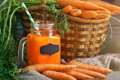 Fresh Carrot and carrot juice on Wooden Table in Garden. Vegetables Vitamins Keratin. Natural Organic Carrot lies on. Wooden background. Rustic Style.Harvest Royalty Free Stock Images