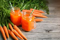 Fresh Carrot and carrot juice on Wooden Table in Garden. Vegetables Vitamins Keratin. Natural Organic Carrot lies on. Wooden background. Rustic Style.Harvest Stock Photo
