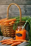 Fresh Carrot and carrot juice on Wooden Table in Garden. Vegetables Vitamins Keratin. Natural Organic Carrot lies on. Wooden background. Rustic Style.Harvest Stock Image