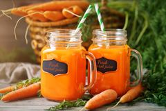 Fresh Carrot and carrot juice on Wooden Table in Garden. Vegetables Vitamins Keratin. Natural Organic Carrot lies on. Wooden background. Rustic Style.Harvest Stock Photos