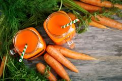 Fresh Carrot and carrot juice on Wooden Table in Garden. Vegetables Vitamins Keratin. Natural Organic Carrot lies on. Wooden background. Rustic Style.Harvest Royalty Free Stock Photography