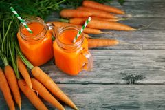 Fresh Carrot and carrot juice on Wooden Table in Garden. Vegetables Vitamins Keratin. Natural Organic Carrot lies on. Wooden background. Rustic Style.Harvest Royalty Free Stock Photo