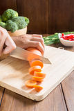 Fresh carrot on cutting board on wooden background. Fresh carrot, whole, sliced on cutting board Royalty Free Stock Photos