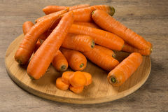 Fresh carrot with green leaves on wooden table Stock Images
