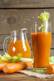 Fresh carrot juice with carrots and celery Royalty Free Stock Images