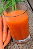 Fresh carrot juice in a glass on rustic wooden table Royalty Free Stock Photos