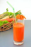 Fresh carrot juice. A glass of fresh carrot juice and vegetables - shallow depth of field royalty free stock images