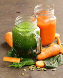 Fresh carrot juice and juice of spinach, celery Royalty Free Stock Photos