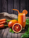 Fresh carrot juice. With oranges at wooden background Royalty Free Stock Images
