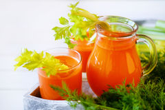 Fresh carrot juice poured into glasses and green celery Stock Photography