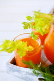 Fresh carrot juice poured into glasses and green celery Stock Photo