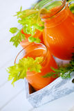 Fresh carrot juice poured into glasses and green celery Royalty Free Stock Photography