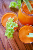 Fresh carrot juice poured into glasses and green celery Stock Image
