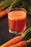 Fresh carrot juice. In a transparent glass on black background with fresh carrots Stock Photography