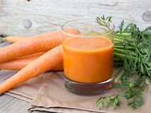 Fresh carrot juice. On a wooden background Royalty Free Stock Images