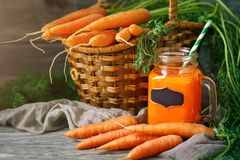 Fresh Carrot and carrot juice on Wooden Table in Garden. Vegetables Vitamins Keratin. Natural Organic Carrot lies on. Wooden background. Rustic Style.Harvest Stock Photography