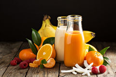 Fresh carrot, orange and coconut juices. In glass bottles Stock Images