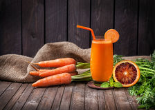 Fresh carrot and orange juice. With oranges at wooden background Royalty Free Stock Photos