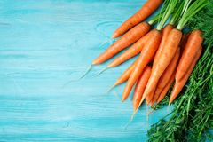Fresh Carrot on Wooden Table in Garden. Vegetables Vitamins Keratin. Natural Organic Carrot lies on Wooden background. Top View Flat Lay. Country Village Stock Photo