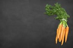 Fresh carrots bunch on blackboard Stock Images