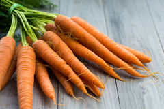 Fresh carrots bunch on wooden background. Fresh carrots bunch on grey wooden background Stock Image
