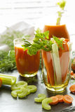 Fresh carrots and celery in glass with fresh carrot juice, dill and parsley Royalty Free Stock Photo