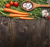 Fresh carrots with cherry tomatoes, garlic and wooden spoon vintage salt and pepper colored it wooden rustic background top vie Stock Image