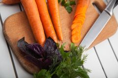 Fresh carrots on a cutting board. Whole and sliced fresh carrots on a cutting board Royalty Free Stock Images